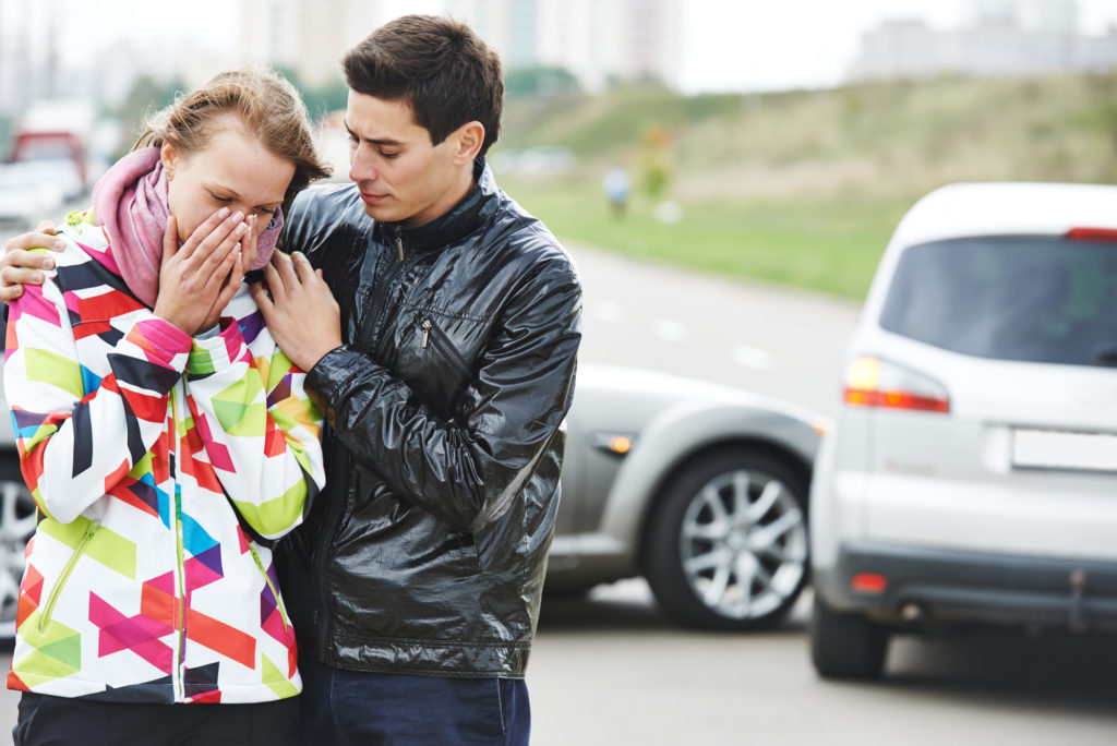 Man consoling woman in front of a car accident