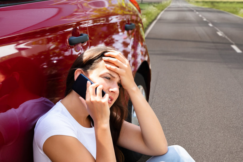 Stressed Woman on the side of the road after a car accident