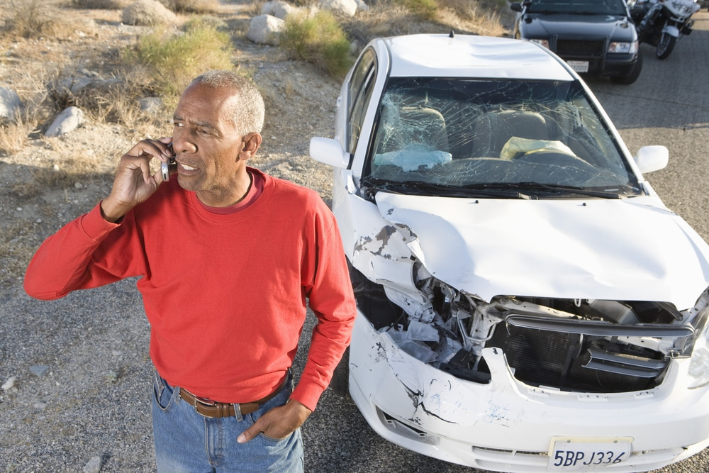 Man on his cell phone after a hit and run car accident with a damaged vehicle behind him