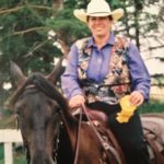 Robinson LLP client Margaret on a horse holding a yellow ribbon